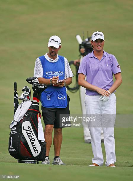 Webb Simpson and his caddie stand in the fairway on the 11th hole during the final round of the Wyndham Championship at Sedgefield Country Club on...