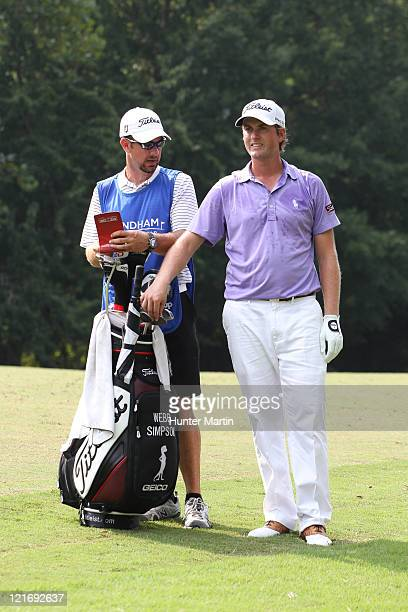 Webb Simpson and his caddie stand in the fairway on the 13th hole during the final round of the Wyndham Championship at Sedgefield Country Club on...