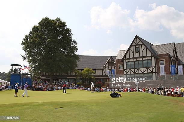Webb Simpson and Tommy Gainey putt on the ninth green during the final round of the Wyndham Championship at Sedgefield Country Club on August 21,...