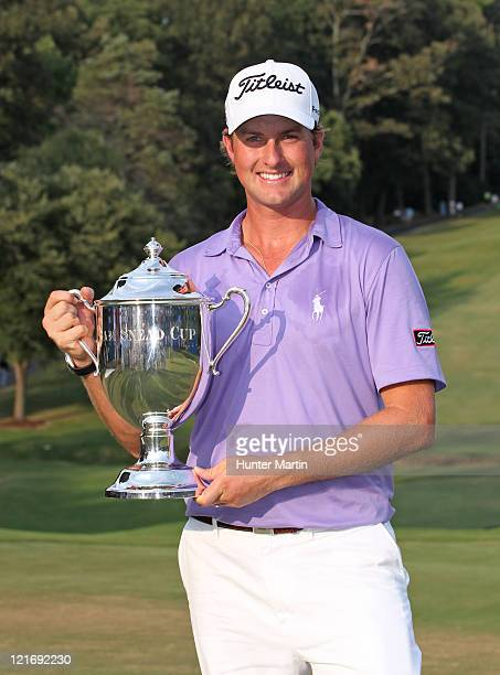 Webb Simpson holds the championship trophy after winning the Wyndham Championship at Sedgefield Country Club on August 21, 2011 in Greensboro, North...