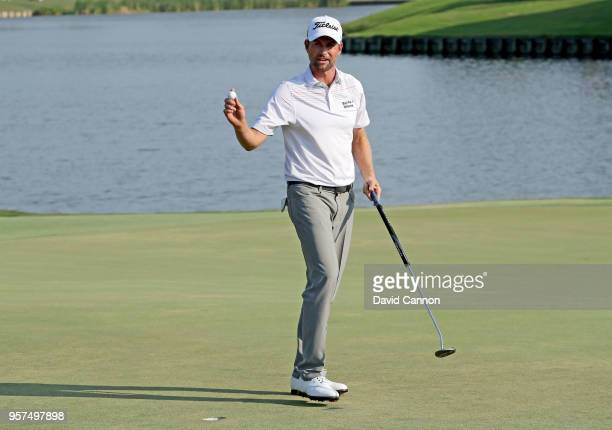 Webb Simpson of the United States acknowledges the crowds on the 18th green after holing out for a course record equalling 10 under par 63 during the...