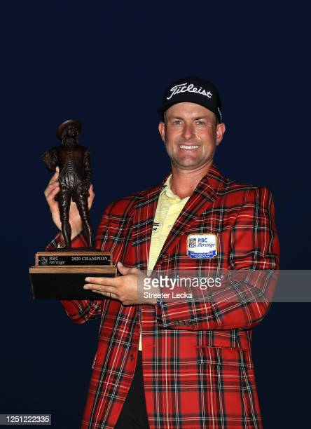 Webb Simpson of the United States celebrates with the trophy and the plaid jacket after winning during the final round of the RBC Heritage on June...