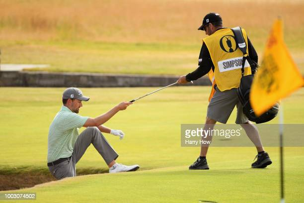 Webb Simpson of the United States is helped out of a bunker by his caddie Paul Tesori on the 18th hole during the third round of the 147th Open...