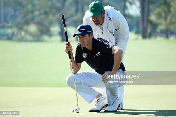 Webb Simpson of the United States lines up a putt on the first green with his caddie Paul Tesori during the first round of the 2014 Masters...