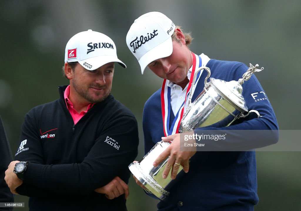 Webb Simpson of the United States (R) looks down at the trophy as Graeme McDowell of Northern Ireland looks on after Simpson's one-stroke victory at the 112th U.S. Open at The Olympic Club on June 16, 2012 in San Francisco, California.