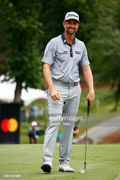 Webb Simpson of the United States reacts after making his second chip on the 18th green for par during the third round of the Wyndham Championship at...