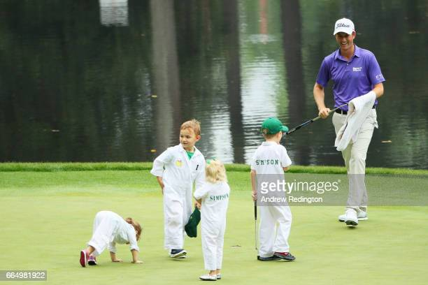 Webb Simpson of the United States smiles alongside his children and Bubba Watson's children during the Par 3 Contest prior to the start of the 2017...