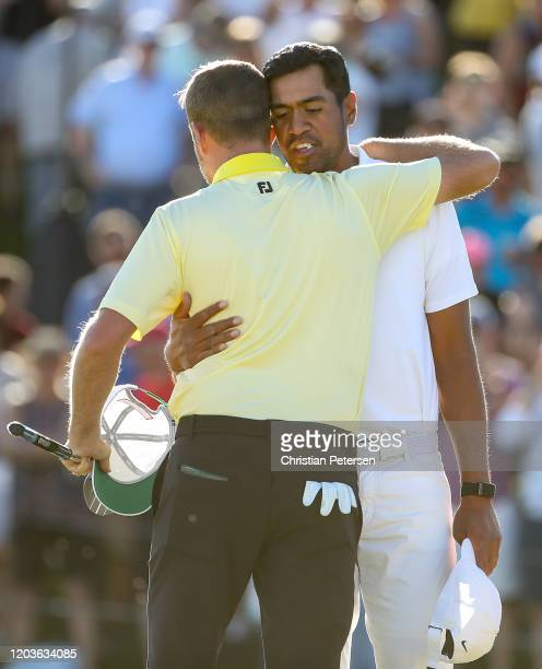 Webb Simpson shakes hands with Tony Finau after defeating him on the first playoff hole during the final round of the Waste Management Phoenix Open...