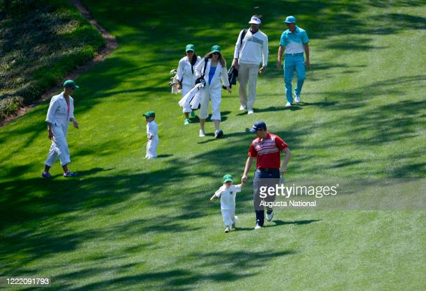 Webb Simpson walks down the No. 1 fairway with his wife Dowd and son James ahead of Masters champion Bubba Watson and his wife Angie and son Caleb...