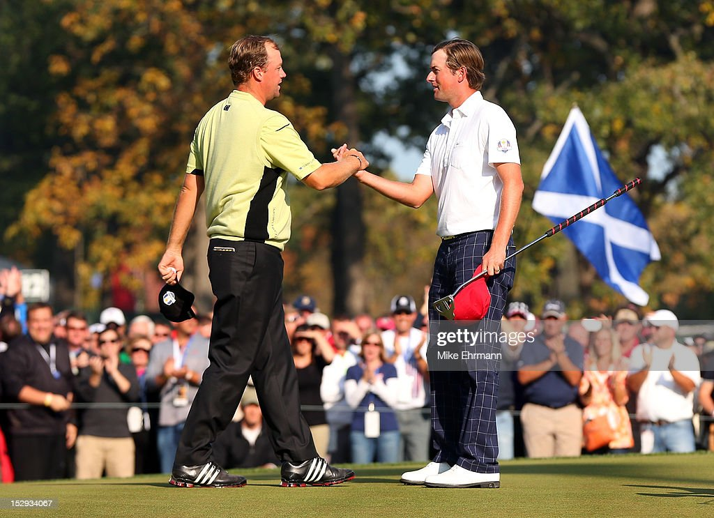 Webb Simpsonof the United States is congratulated by Peter Hanson on the 14th green after defeating the Lawrie/Hanson team 5&4 during the Afternoon Four-Ball Matches for The 39th Ryder Cup at Medinah Country Club on September 28, 2012 in Medinah, Illinois.