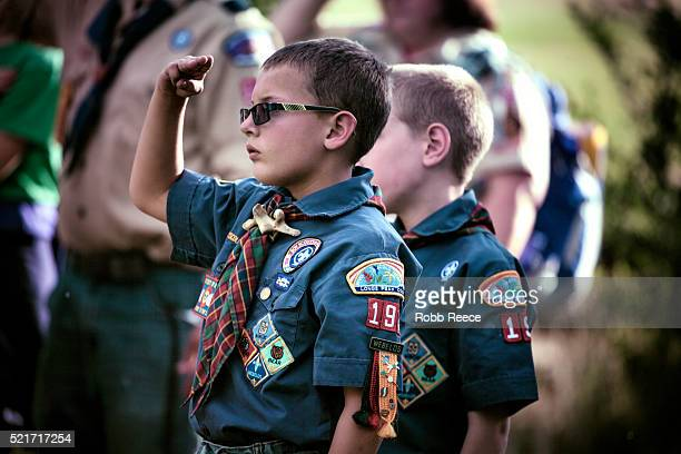 a weblo boy scout salutes an american flag raising during a ceremony at their camp in colorado. - robb reece stock pictures, royalty-free photos & images