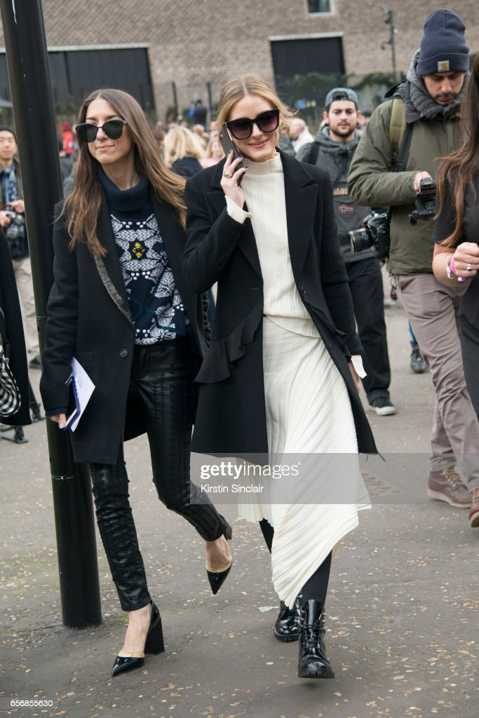 Website'u2019s director of partnerships and editorial coordinator for Olivia Palermo Jilian Magenheim wears a Barrie sweater, Blank NYC trousers and Kendall Miles shoes with Model and Actress Olivia Palermo wearing a Topshop skirt and sweater, Dior jacket and Chanel boots on day 3 of London Womens Fashion Week Autumn/Winter 2017, on February 19, 2017 in London, England.