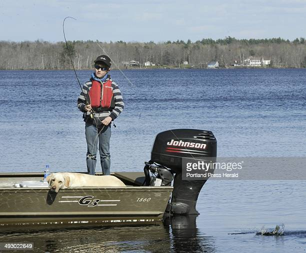 Wed Kevin McKay has taught his two young sons to fly fish 10 year old Tait hooks and plays a black crappie as his dog Feta watches on Hermon Pond