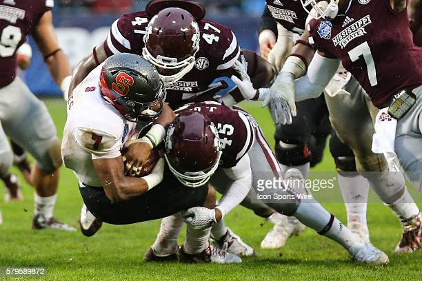 North Carolina State Wolfpack wide receiver Nyheim Hines is wrapped up by Mississippi State Bulldogs defensive lineman AJ Jefferson and linebacker JT...