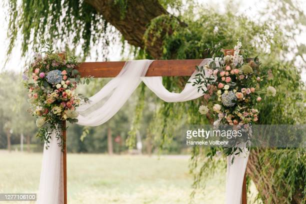 wedding arch decorated with flowers and greenery in rural area - ceremony stock pictures, royalty-free photos & images
