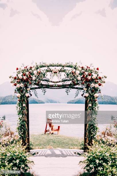 wedding arch decorated with flowers and greenery near lake or river outdoors - arch stock pictures, royalty-free photos & images