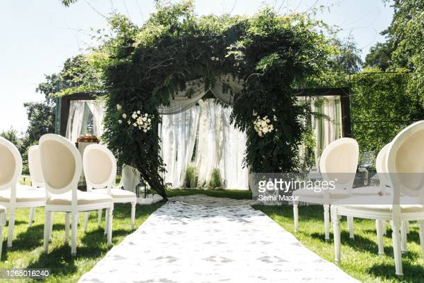 wedding arch decorated with greenery outdoors - stock photo - wedding stock pictures, royalty-free photos & images
