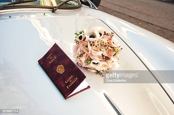 Wedding bouquet and newlyweds' family book on car bonnet in Nice, France