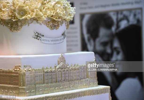 A wedding cake and portraits are displayed during the launch of an exhibition commemorating the royal wedding of Britain's Prince Harry and US...