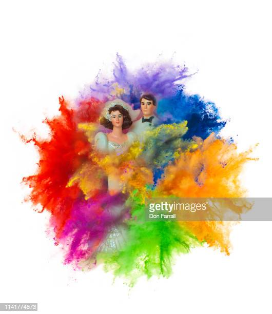 wedding cake couple in exploding multi colored powder - don farrall stock pictures, royalty-free photos & images