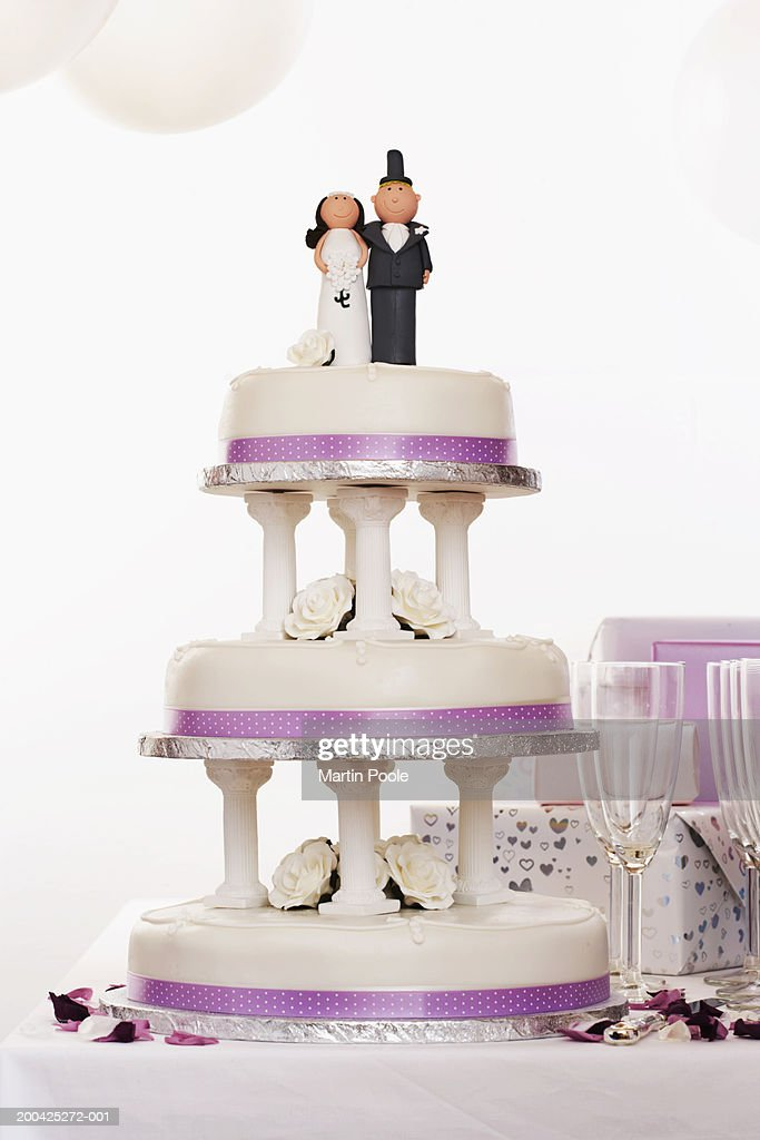 Wedding cake decorated with bride and groom figures on table by gifts : Stock Photo