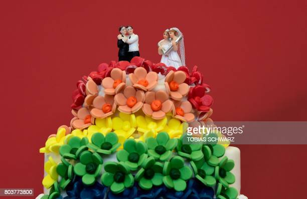 TOPSHOT A wedding cake in rainbow colors and decorated with figurines of two women and two men is pictured in Berlin on June 30 2017 The German...