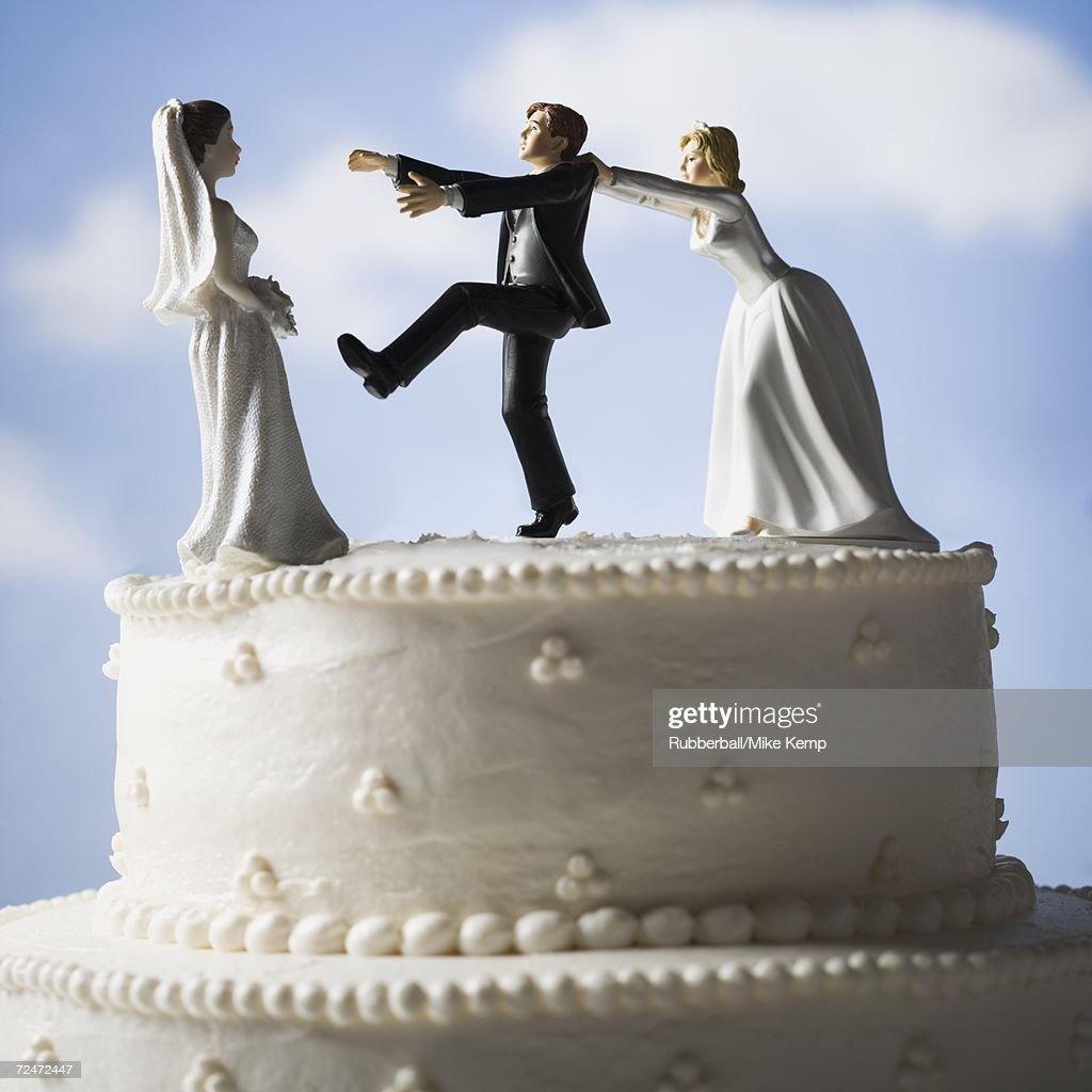 Wedding cake visual metaphor with figurine cake toppers : Stock Photo