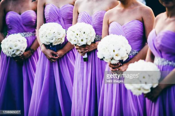 wedding ceremony with bridesmaids wearing purple dresses and holding white flowers. - bridesmaid stock pictures, royalty-free photos & images