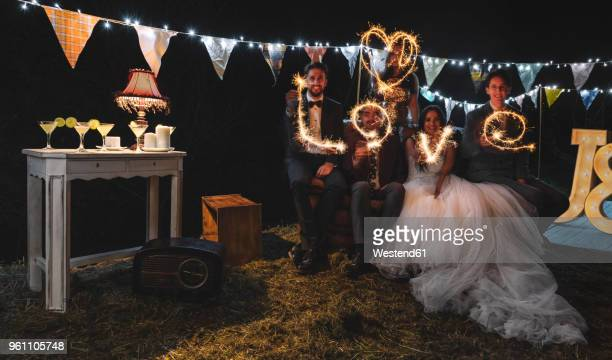 Wedding couple and friends making the word love with sparklers on a night party outdoors