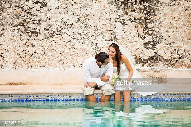 Wedding couple by a pool relaxing