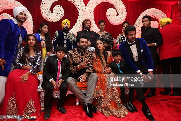 Wedding couple Daler Mehndis daughter Ajit Kaur and Navraj Singh son of singer Hans Raj Hans pose with their family during prewedding party on...