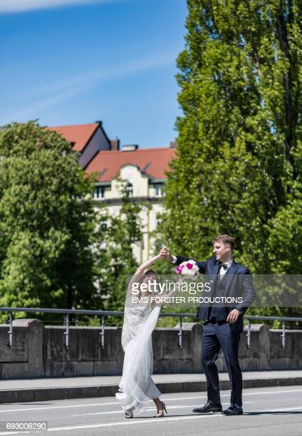 wedding couple in their festive clothes walking happy and careless with a big smile on a city street, he wears his wedding suit with fly and she her white wedding dress with vein, she holds her bridal flowers consisting of white and pink peonies