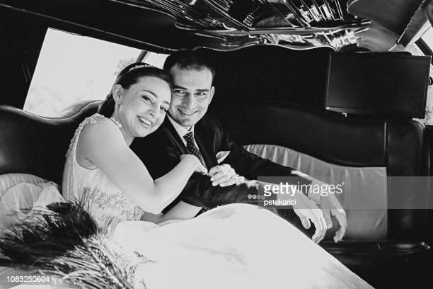 wedding couple inside elegance limousine at their wedding day - marriage stock pictures, royalty-free photos & images