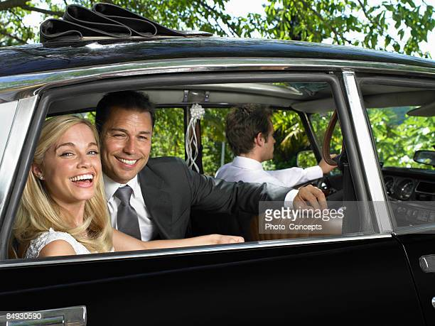 Wedding couple laughing in car