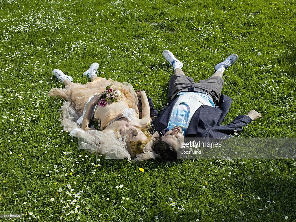 wedding couple lying on grass : Stock Photo