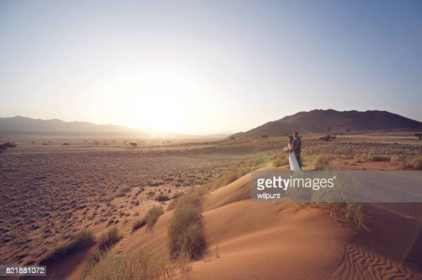 Wedding Couple on sand dune at sunset