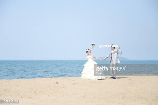 ビーチでの結婚式のカップル - ハネムーン ストックフォトと画像