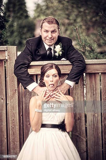 wedding couple outdoors over a fence - women being strangled stock photos and pictures