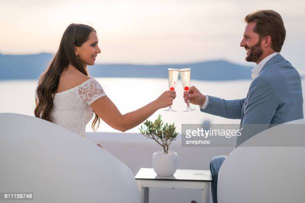 wedding couple sitting above caldera cheering with champagne
