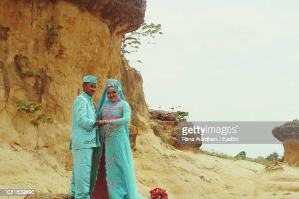wedding couple standing against rock formation - 民族衣装 ストックフォトと画像