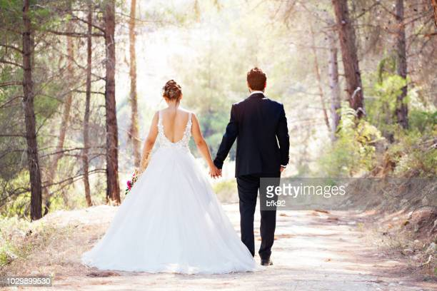 wedding couple walking on road. - newlywed stock pictures, royalty-free photos & images