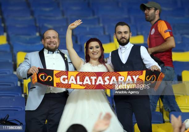 A wedding couple who are Galatasaray fans watch the Turkish Super Lig soccer match between Genclerbirligi and Galatasaray at the Eryaman Stadium in...