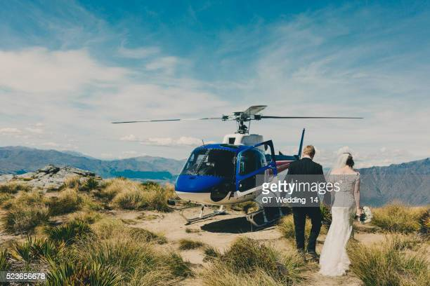 wedding day - couple walk to helicopter on mountain, queenstown, nz - helicopter photos stock pictures, royalty-free photos & images