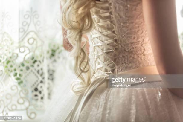 wedding day preparation with the back of the bride's corset detail. - korsett stock-fotos und bilder