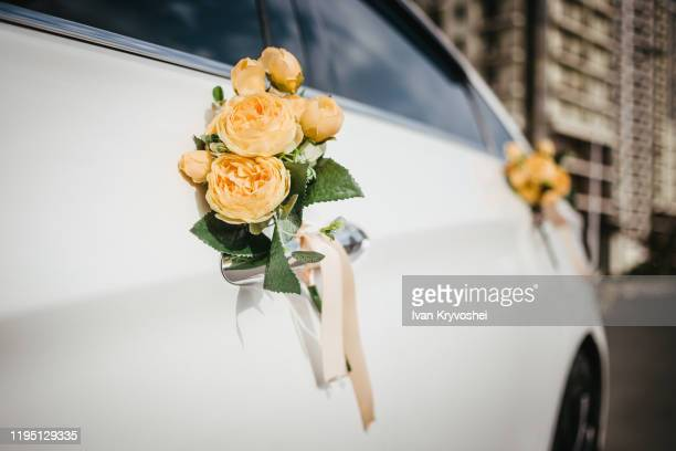 wedding decor on the car handle. flower decoration with ribbons on a white car - wedding decoration stock pictures, royalty-free photos & images