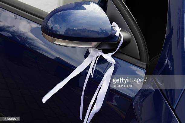 Wedding decoration at the wing mirror of a car
