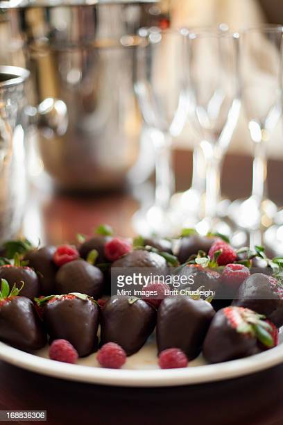 wedding dessert. plate of hand-dipped organic strawberries, fruit in artisanal handmade chocolate with raspberry garnish. - utah wedding stock pictures, royalty-free photos & images