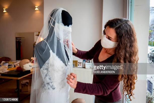 Wedding dress and evening wear designer Friederike Jorzig adjusts a mannequin wearing a wedding dress with matching protective mask in her store...
