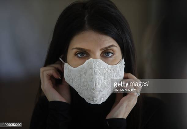 Wedding dress designer Lobna Safadi from the Druze village of Majdal Shams in the Israel-annexed Golan Heights models an embroidered protective mask...