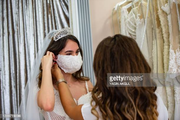 Wedding Dress designer Pinar Bent adjusts a mannequin wearing a wedding dress with matching protective mask in her store in Istanbul on June 30 2020...